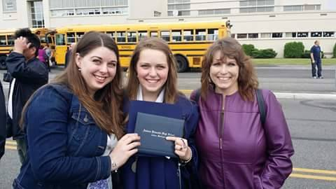 Kelsey (center) showing off her high school diploma